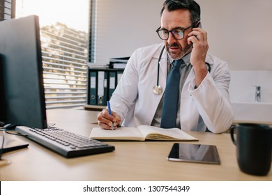 Doctor talking over his mobile phone and making notes in a book. Medicine professional talking on phone and writing in his diary.