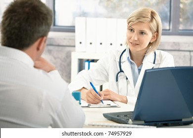 Doctor talking to patient in office, taking notes, smiling.?