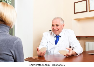 doctor talking to patient, show breast implant office desk, plastic surgery young girl mature