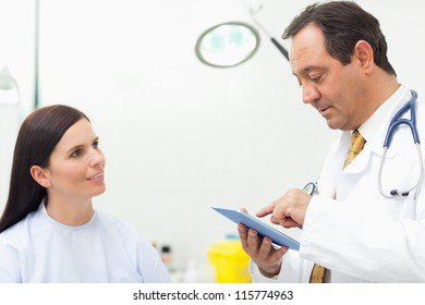 Doctor talking with a patient while using a tablet in an examination room
