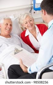 Doctor talking to senior couple on UK Hospital ward