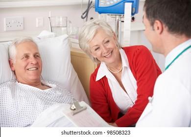Doctor talking to senior couple on USA Hospital ward