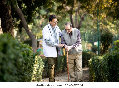 Doctor talking with senior man in hospital garden