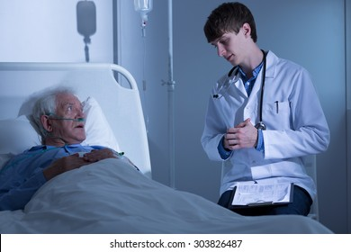 Doctor talking with terminally ill senior man