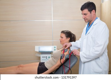 Doctor therapist checking arm shoulder muscle electrostimulation to woman in hospital
