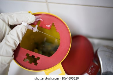 doctor throws the syringe and needle into the container for disposal
