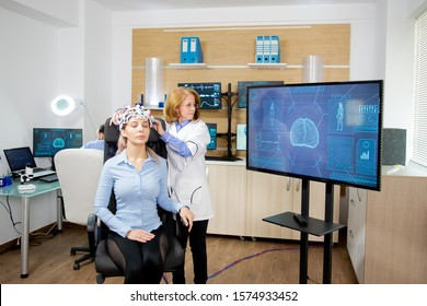 Doctor tracking the data transmitted by the brainwaves scanning headset on a large monitor. Modern equipment