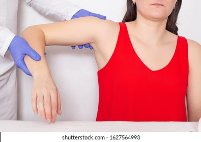 Doctor traumatologist examines a broken shoulder in a girl athlete. The concept of injury in athletes, dislocation of the shoulder
