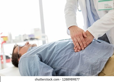 Doctor treating stomach of patient in examination room