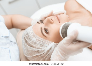 The doctor treats the girl's face with a photoepilator. The girl is lying on the couch in a modern cosmetology salon. She smiles.