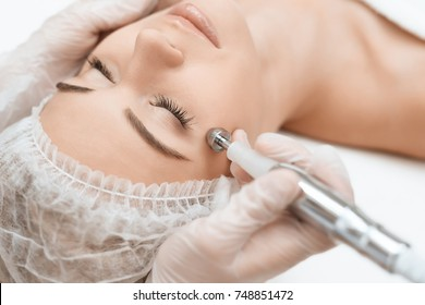 The doctor treats the girl's face with a photoepilator. The girl is lying on the couch. The doctor treats the girl's skin around the eyes. They are in a modern beauty salon.