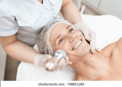 The doctor treats the male skin with a photoepilator. The man is lying on the couch and is smiling. They are in a modern beauty salon.