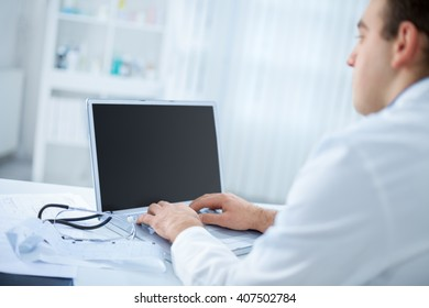 Doctor typing on the computer in his office