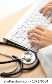 Doctor typing on keyboard with stethoscope