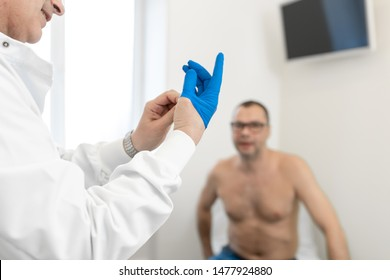 Doctor urologist puts a medical glove on the arm to examine the patient's prostate, prostate massage, lymphatic drainage.