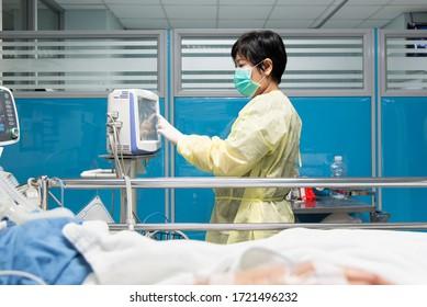 Der Arzt verordnet ein Monitoring mit Vitalzeichen für die medizinische Versorgung der Grippe covid19, Corona-Virus, CRE. oder VRE. infizierter älterer Patient im Alter von 80 Jahren im Patientenbett in einem Intensivpflegeraum im Krankenhaus
