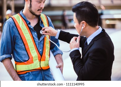 Doctor uses stethoscope to check the heart engineer and worker on building site.