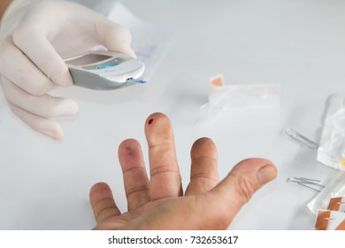 The doctor is using a blood collection device to detect blood sugar.