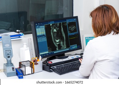 Doctor using computer to analyzing brain MRI in radiology room of the hospital