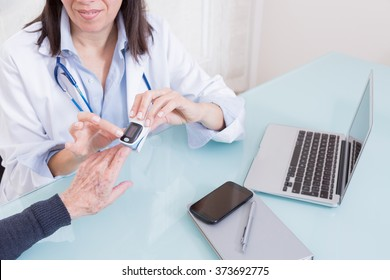 Doctor using finger pulse oximeter with patient. Unrecognizable. From above
