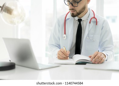 Doctor using laptop and electronic medical record (EMR) system. Digital database of patient's health care and personal information on computer screen. Hand writing report.