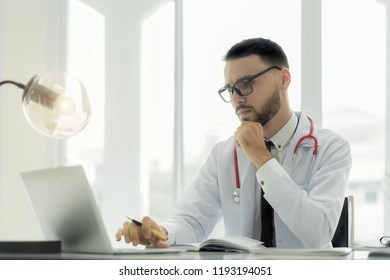 Doctor using laptop and electronic medical record (EMR) system. Digital database of patient's health care and personal information on computer screen.