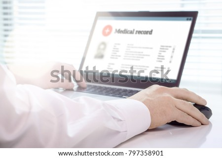 Doctor using laptop and electronic medical record (EMR) system. Digital database of patient's health care and personal information on computer screen. Hand on mouse and typing with keyboard.