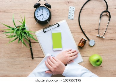 Doctor using smartphone app in hospital office, overhead view of female person hands holding mobile phone with blank screen as mock up copy space