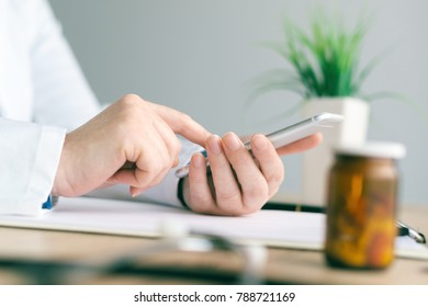 Doctor using smartphone app in hospital office, close up of female person hands holding mobile phone. Modern technology in health care and medicine.