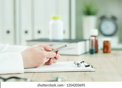 Doctor using smartphone in medical office, close up of hands