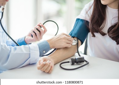 Doctor using sphygmomanometer with stethoscope checking blood pressure to a patient in the hospital.