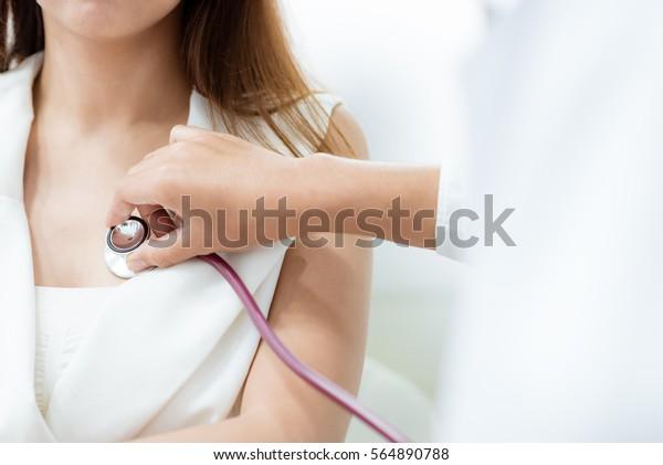 Doktor, der das Stethoskop zur Untersuchung des Herzens von Patientinnen anwendet