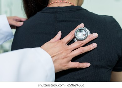 Doctor using stethoscope listening to the lung sounds.