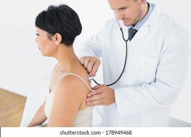 Doctor using stethoscope on back of female patient in clinic