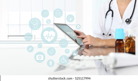 doctor using tablet in medical office with drugs on desk and icons