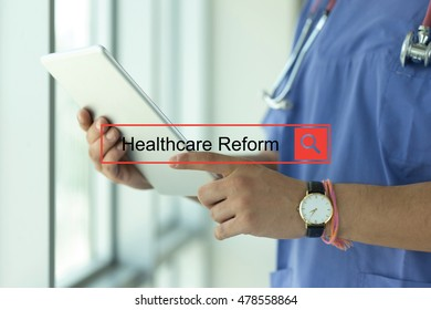 DOCTOR USING TABLET PC SEARCHING HEALTHCARE REFORM