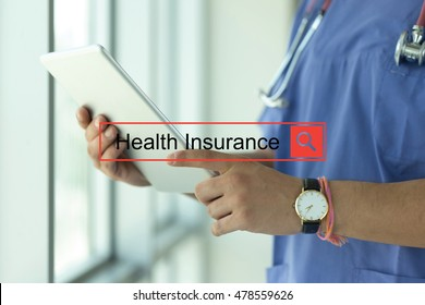 DOCTOR USING TABLET PC SEARCHING HEALTH INSURANCE