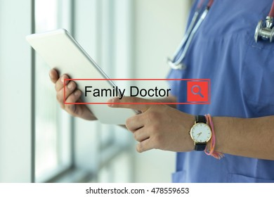 DOCTOR USING TABLET PC SEARCHING FAMILY DOCTOR