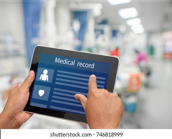 Doctor using tablet to search and check patient medical records in hospital ICU unit.