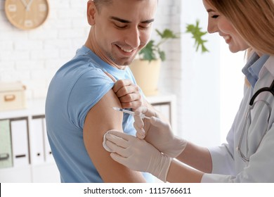 Doctor vaccinating male patient in clinic