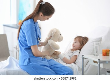 Doctor visiting little girl in hospital room