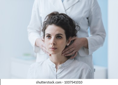 Doctor visiting a patient at the hospital, she is examining her throat and checking glands with her hands