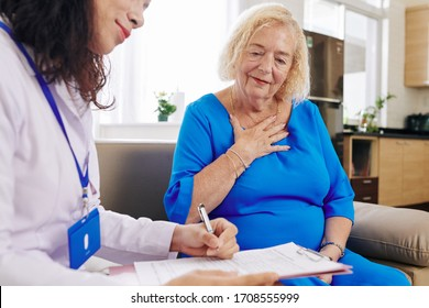 Doctor visiting senior woman at home and writing down her complaints in medical document