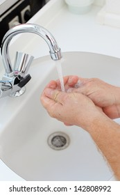 doctor washing hands in white basin in clinic