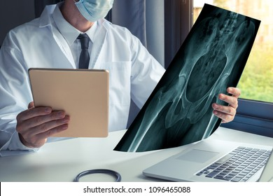 Doctor watching a x-ray of bones of hips and holding a digital tablet with laptop