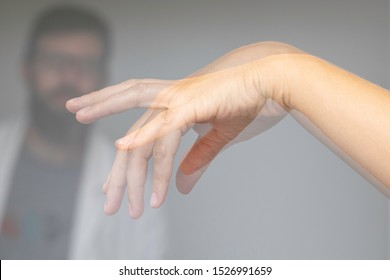 Doctor wathing shaking hand of a person suffering from Parkinson's disease
