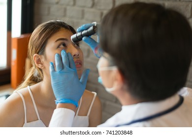 The doctor wear white coat shines a flashlight at the eyes of a female patient at a clinic. Concept of Healthcare, Medical treatment , examination