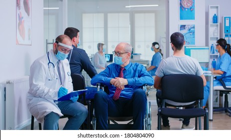 Doctor wearing face mask and visor against infection with coronavirus while talking with disabled senior man in waiting area sitting on wheelchair. Patient and nurse at clinic reception.