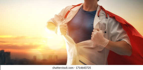 Doctor wearing facemask and superhero cape during coronavirus outbreak. Virus and illness protection, quarantine. COVID-2019. Super hero power for  medicine. Person on sunset cityscape background.