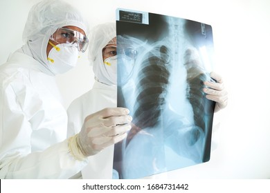Doctor are wearing PPE and  examining a lung radiography coronavirus covid 19 disease virus infected patient's laboratory report.